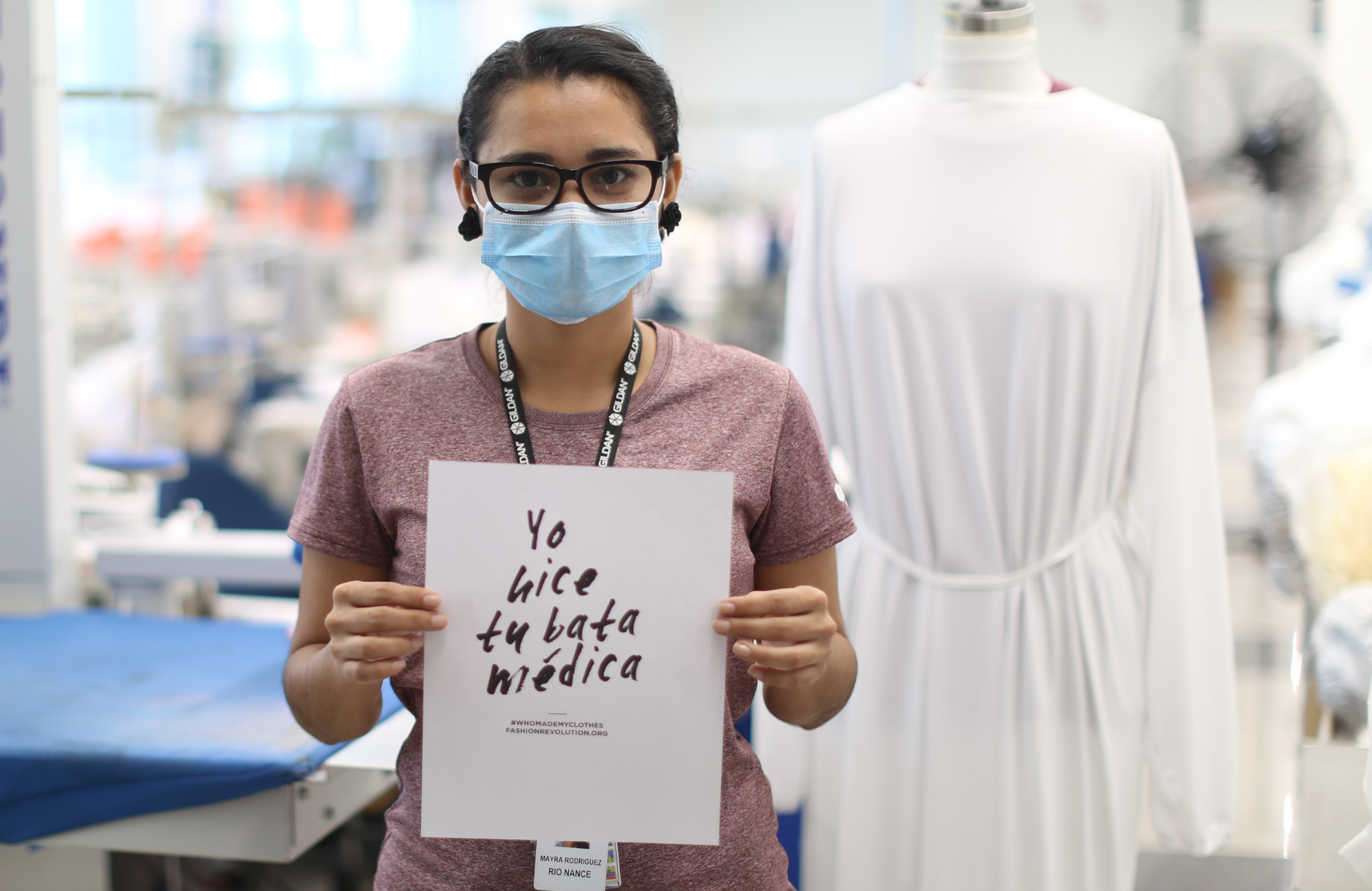 "Employee Mayra Rodriguez holding a sign that reads ""I made your medical gown"""